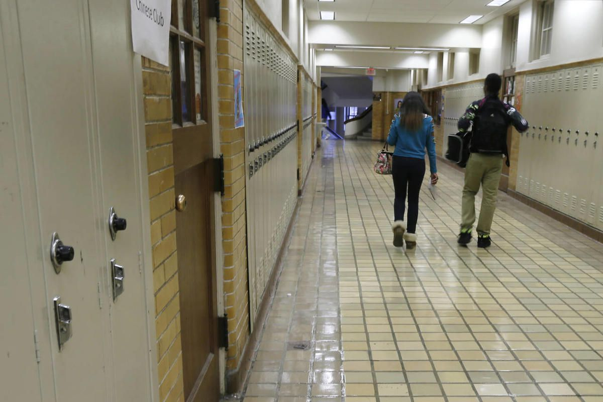 """Two students walk in a high school hallway in this Monday, Jan. 13, 2014, photo. A prominent group of educators is pushing a concept known as """"controlled choice,"""" which allows parents to choose schools by ranking their preferences, especially in urban are"""