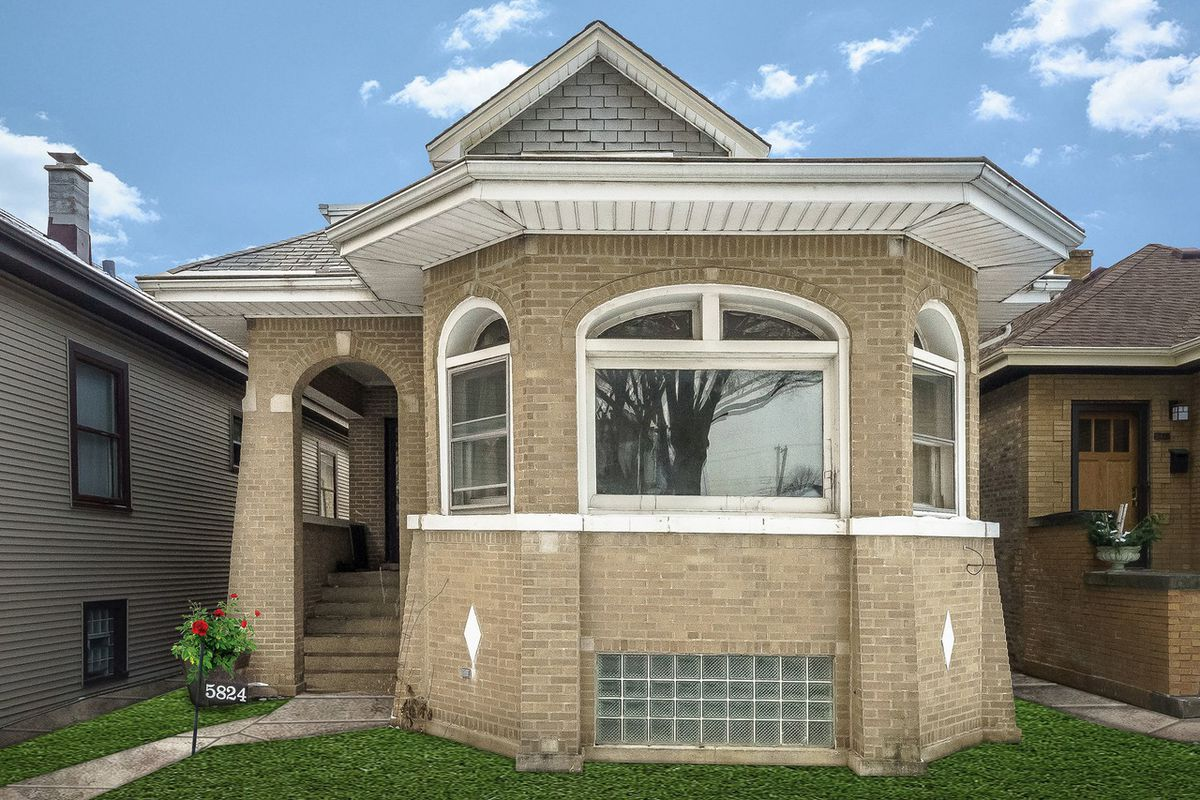 A bungalow with beige brick, a front window, and white trim.