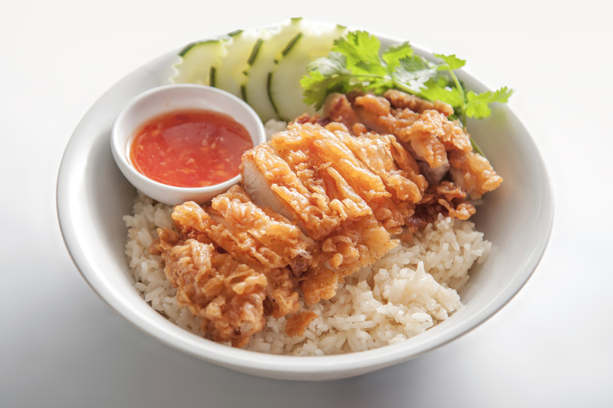 A bowl of light-colored fried chicken rests atop rice next to cucumber, greens, and a side of red chili sauce