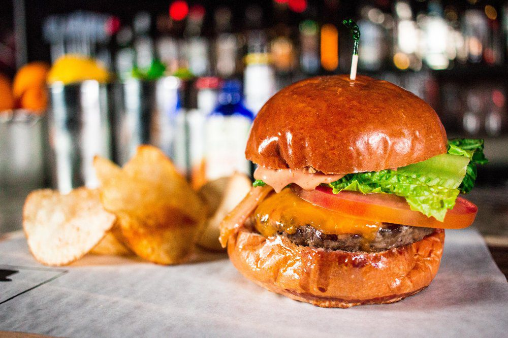 A burger served in a tall bun with a side of potato chips.