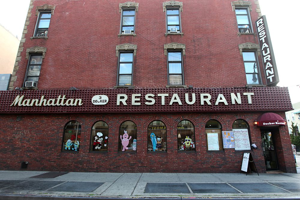 "A tall brick building with a sign that says ""Manhattan Three Decker Restaurant"""
