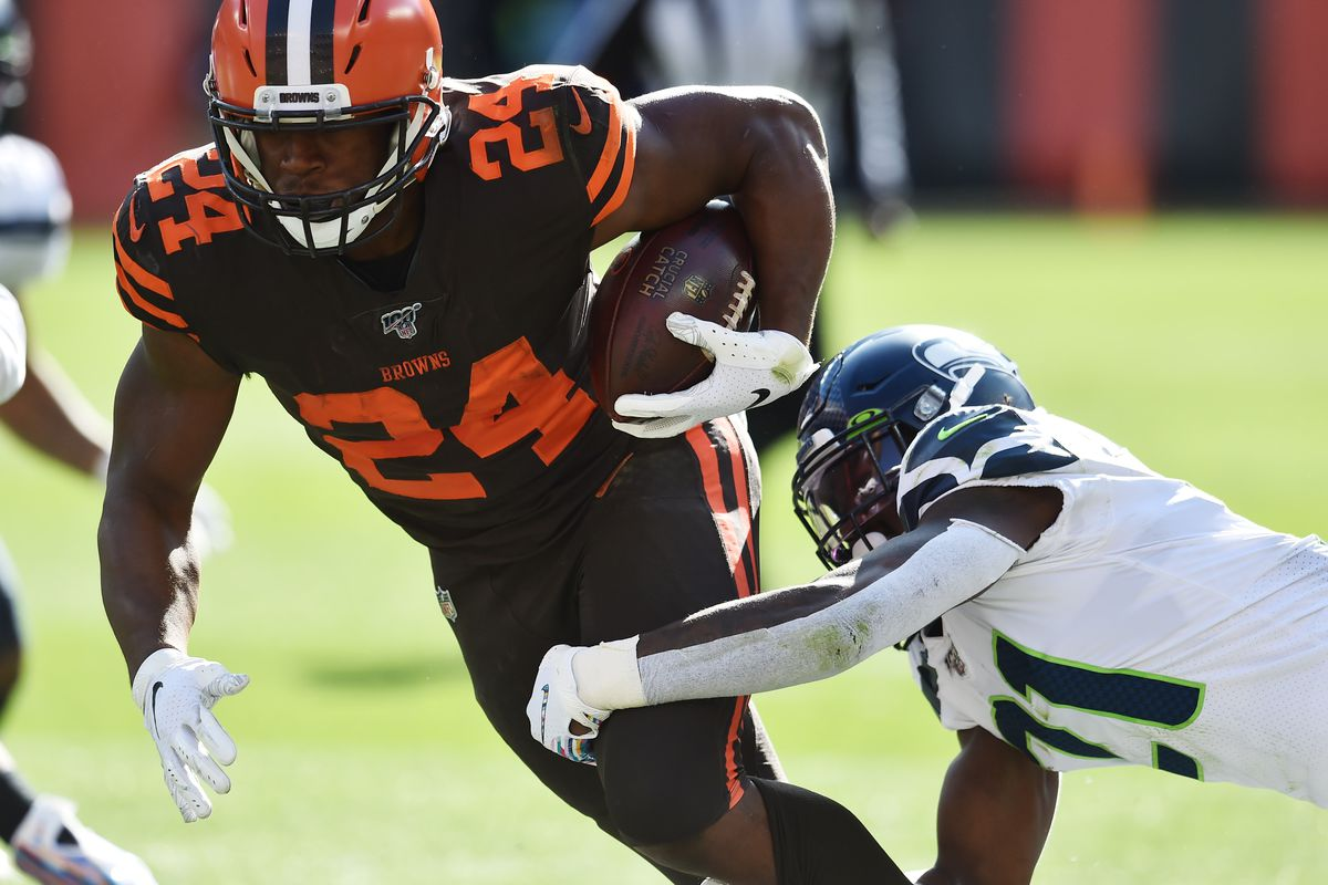 Cleveland Browns running back Nick Chubb runs with the ball as Seattle Seahawks cornerback Tre Flowers defends during the second half at FirstEnergy Stadium.