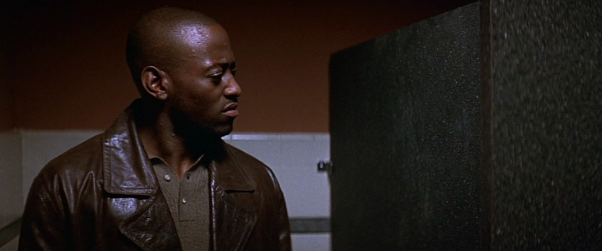 phi (omar epps) stands in a bathroom stall making a face at the wall