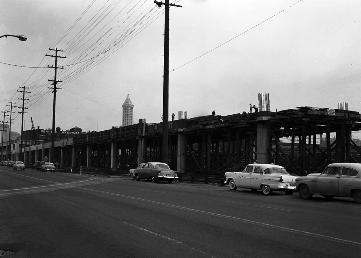 A street with cars and a viaduct. This is a historic black and white photograph.