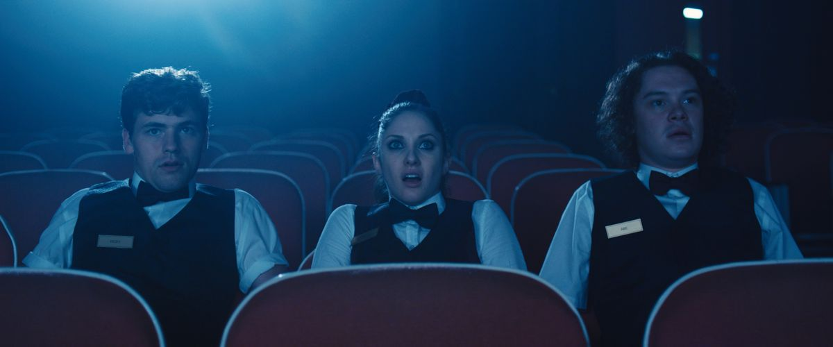 Two young men and a woman dressed as movie-theater ushers sit in a movie theater alone, staring at the screen in shock.