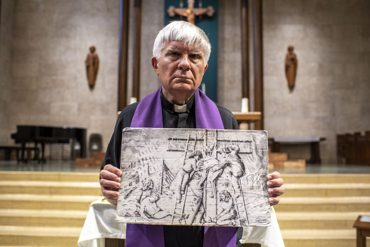"""Father Bruce Nieli poses for a photo while holding a painting by Alice McMahon White depicting Jesus at New York's ground zero at St. Austin Catholic Parish in Austin, Texas, on Thursday, Sept. 9, 2021. Father Nieli was at ground zero shortly after the Sept. 11 attacks when officials made the largest discovery of bodies since the attack. Through his experience, Father Nieli came to better develop a """"spirit of reconciliation and peace."""""""