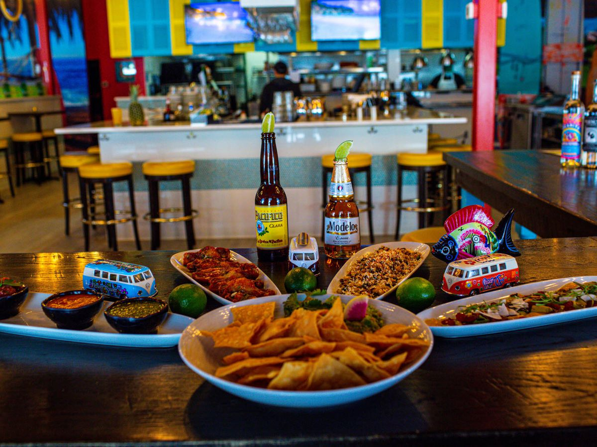 A spread of nachos with salsas in front of the bar inside the California surf-styled Baja Haus