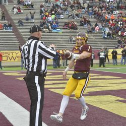 Tommy Lazzaro hands the ball to the back judge after scoring a touchdown to put CMU up 14-0 in the first quarter.
