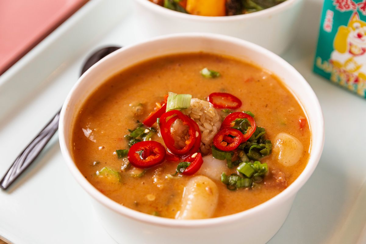White scallops float near the top of a light red gumbo, garnished with crimson chiles and scallions