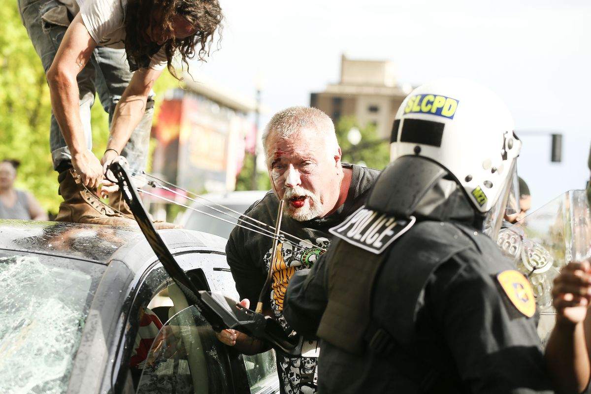 A man exits his car with a bow and arrow after being swarmed by protesters near Library Square in Salt Lake City on Saturday, May 30, 2020. Protesters joined others across the nation to decry the death of George Floyd, a black man, who died while being taken into custody by police in Minneapolis earlier this week.