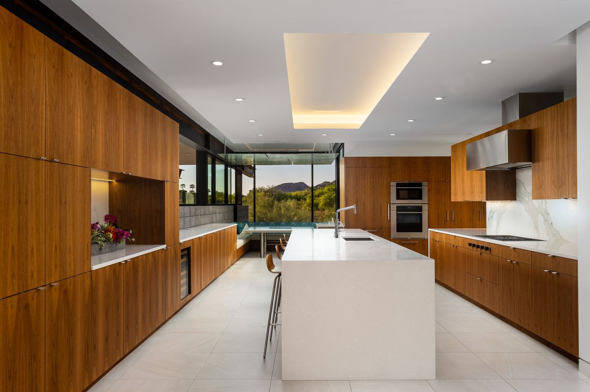 An open kitchen with a white island and wooden cabinets.