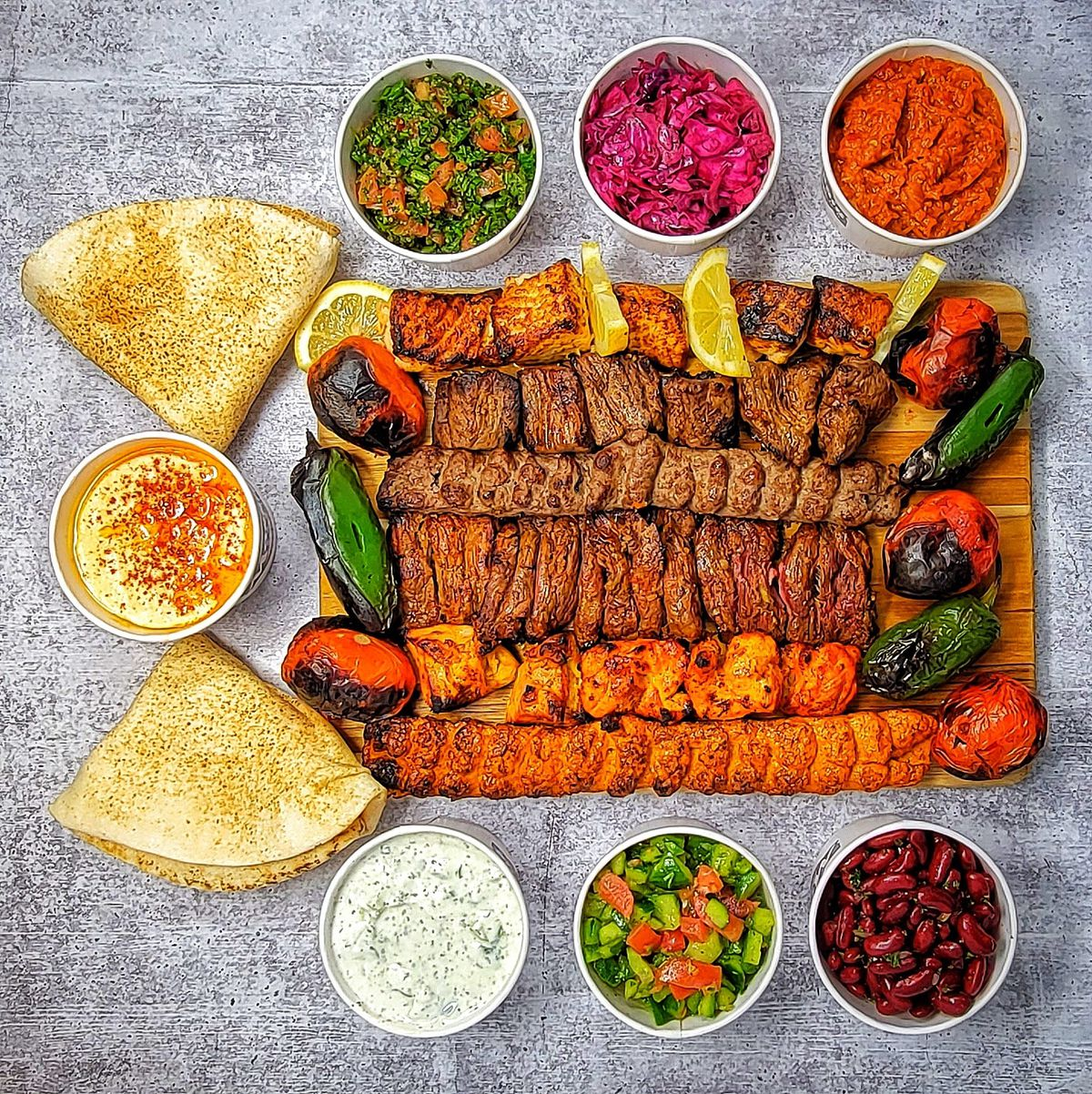 An overhead shot of meat kebabs on a wooden plank, surrounded by side dishes and pita.