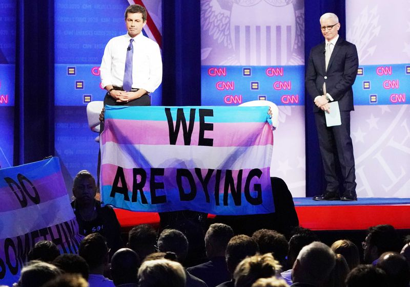 """Protester holds up a banner reading """"We Are Dying"""" in front of Pete Buttigieg and Anderson Cooper."""