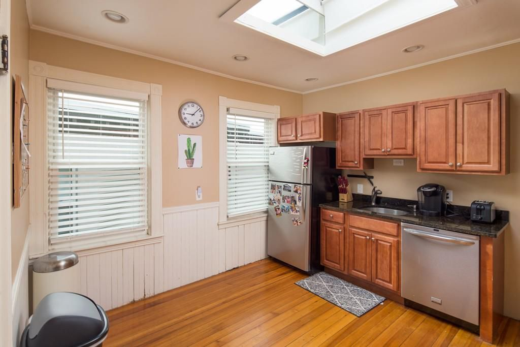 A largely empty kitchen with one counter and two windows.