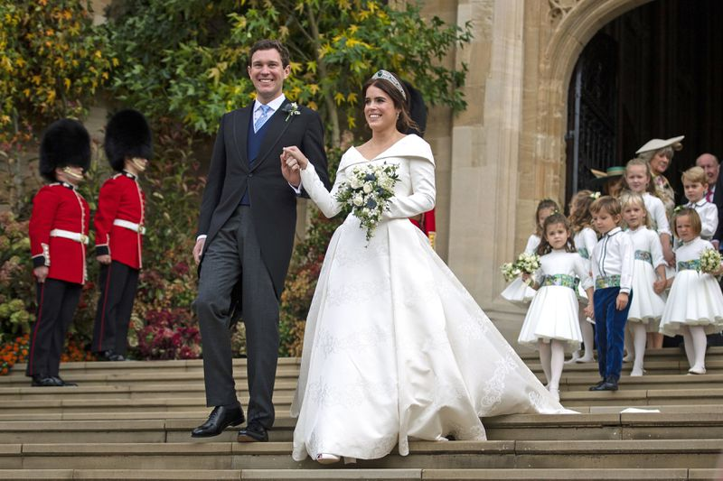 The couple hold hands and walk down the chapel's stairs.