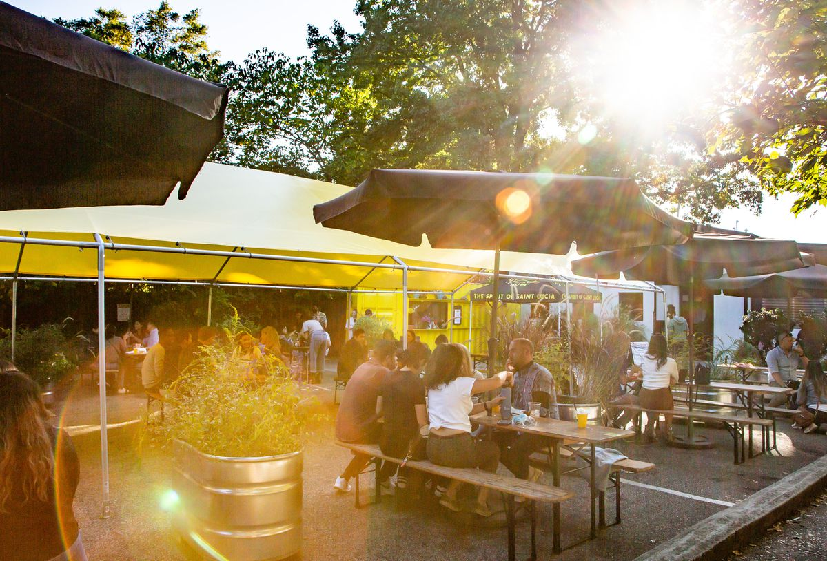 People sitting outside at picnic tables scattered about the parking lot, some under a long yellow tent, at Victory Sandwich Bar in Inman Park, Atlanta. Sunlight pops through the trees as evening sets in