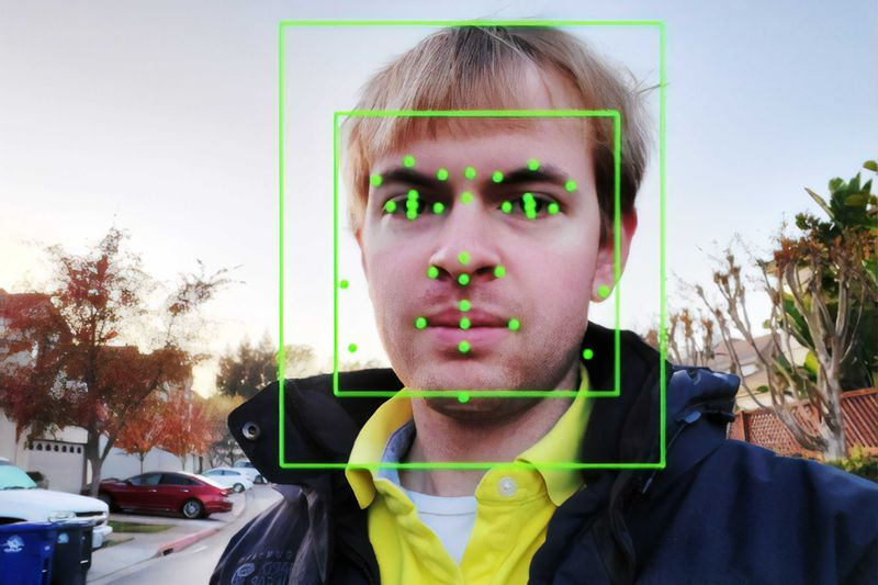Facial recognition boxes and dots cover the photo of a blond man.