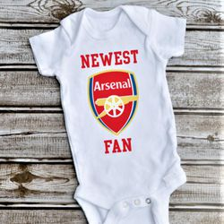 """<a class=""""ql-link"""" href=""""https://www.etsy.com/listing/641765879/newest-fan-arsenal-fan-baby-bodysuit?ga_order=most_relevant&ga_search_type=all&ga_view_type=gallery&ga_search_query=arsenal+gifts&ref=sr_gallery-1-37&frs=1"""" target=""""_blank"""">Arsenal onesie</a>. What else is the baby going to wear on matchday? For the newest Gooners. Well, maybe for their parents. From <a class=""""ql-link"""" href=""""https://www.etsy.com/shop/DesignsbyAZShop?ref=simple-shop-header-name&listing_id=641765879"""" target=""""_blank"""">DesignsbyAZShop</a>."""