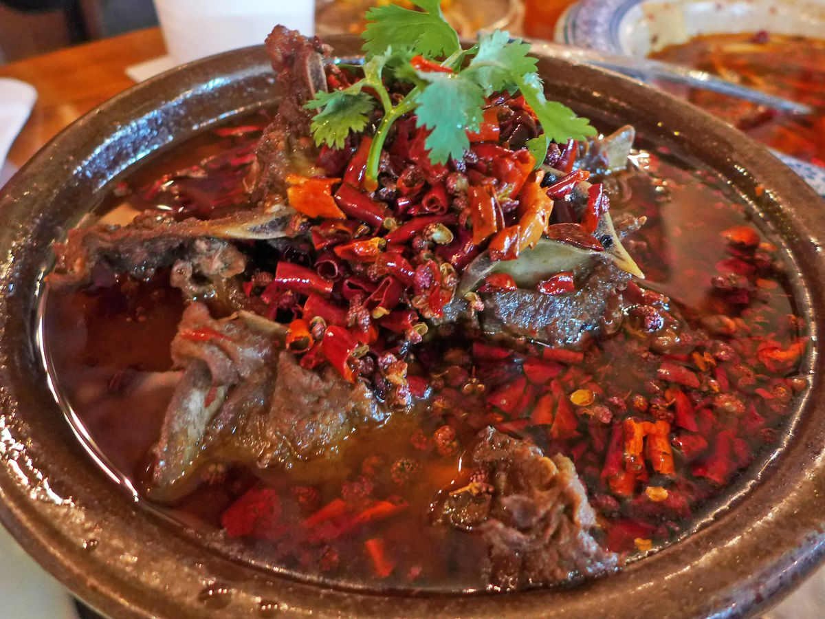 Bony hunks of lamb in red oil with chopped red peppers sprinkled all around.