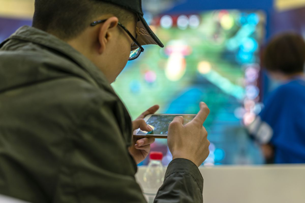 A young man plays a mobile game on his phone.