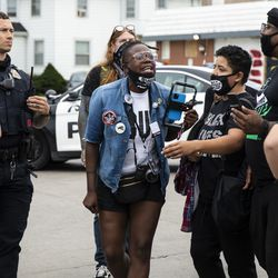A Black Lives Matter protester yells at Kenosha police officers after she was pepper-sprayed during a skirmish with a member of the Proud Boys, a far-right extremist organization, and a woman wearing a MAGA hat near the Kenosha County Courthouse, Tuesday evening, Sept. 1, 2020. President Donald Trump visited Kenosha Tuesday after the police shooting of Jacob Blake led unrest in the Wisconsin city.
