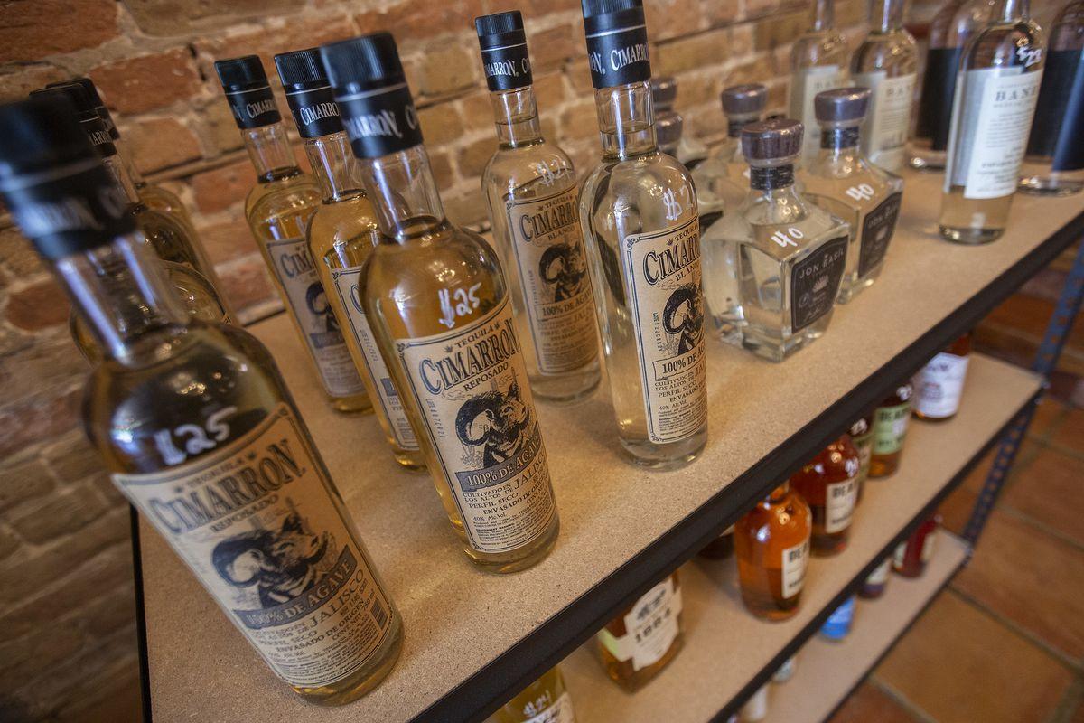 A shelf full of bottles of tequila and liquor.