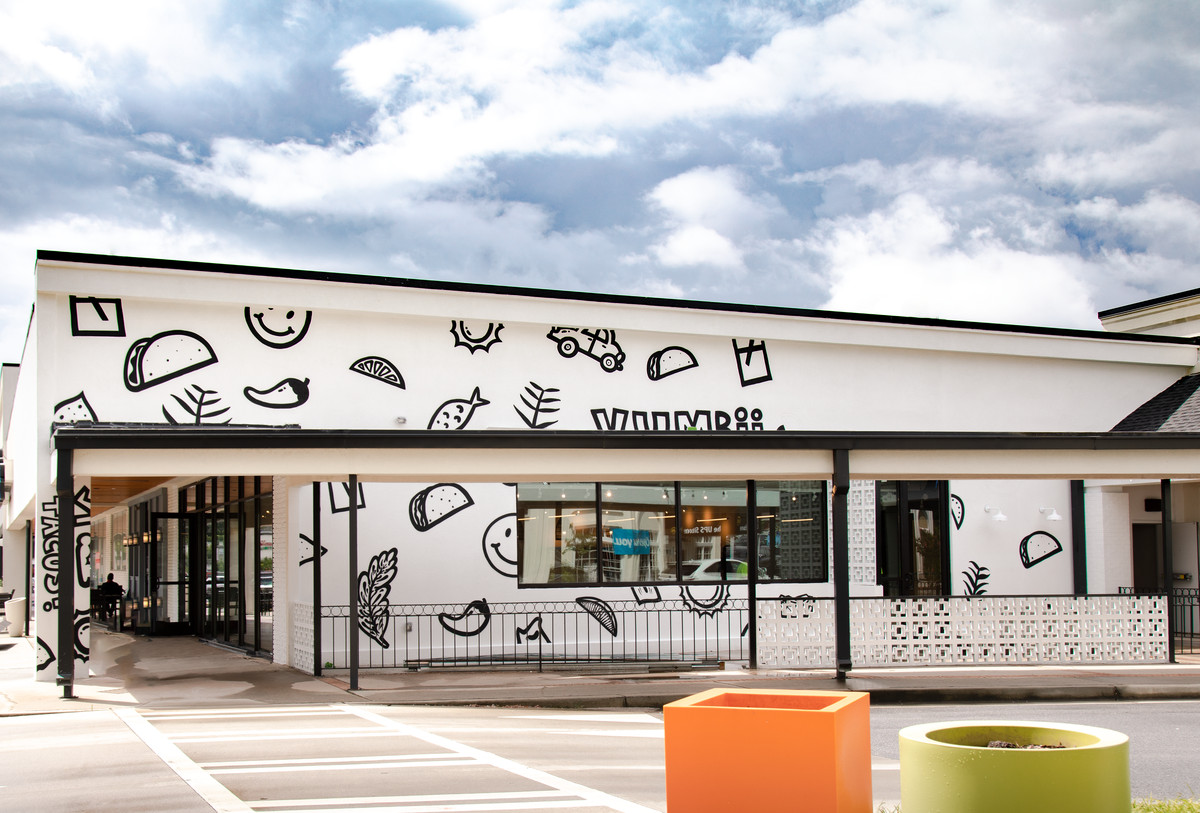 The white-washed exterior of Yumbii in Toco Hills with hand-painted images of tacos, fish, cars, and smiley faces on the side of the building