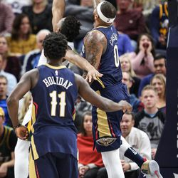 Utah Jazz guard Donovan Mitchell (45) does a reverse layup past New Orleans Pelicans center DeMarcus Cousins (0) as Utah hosts New Orleans at Vivint Arena in Salt Lake on Friday, Dec. 1, 2017.