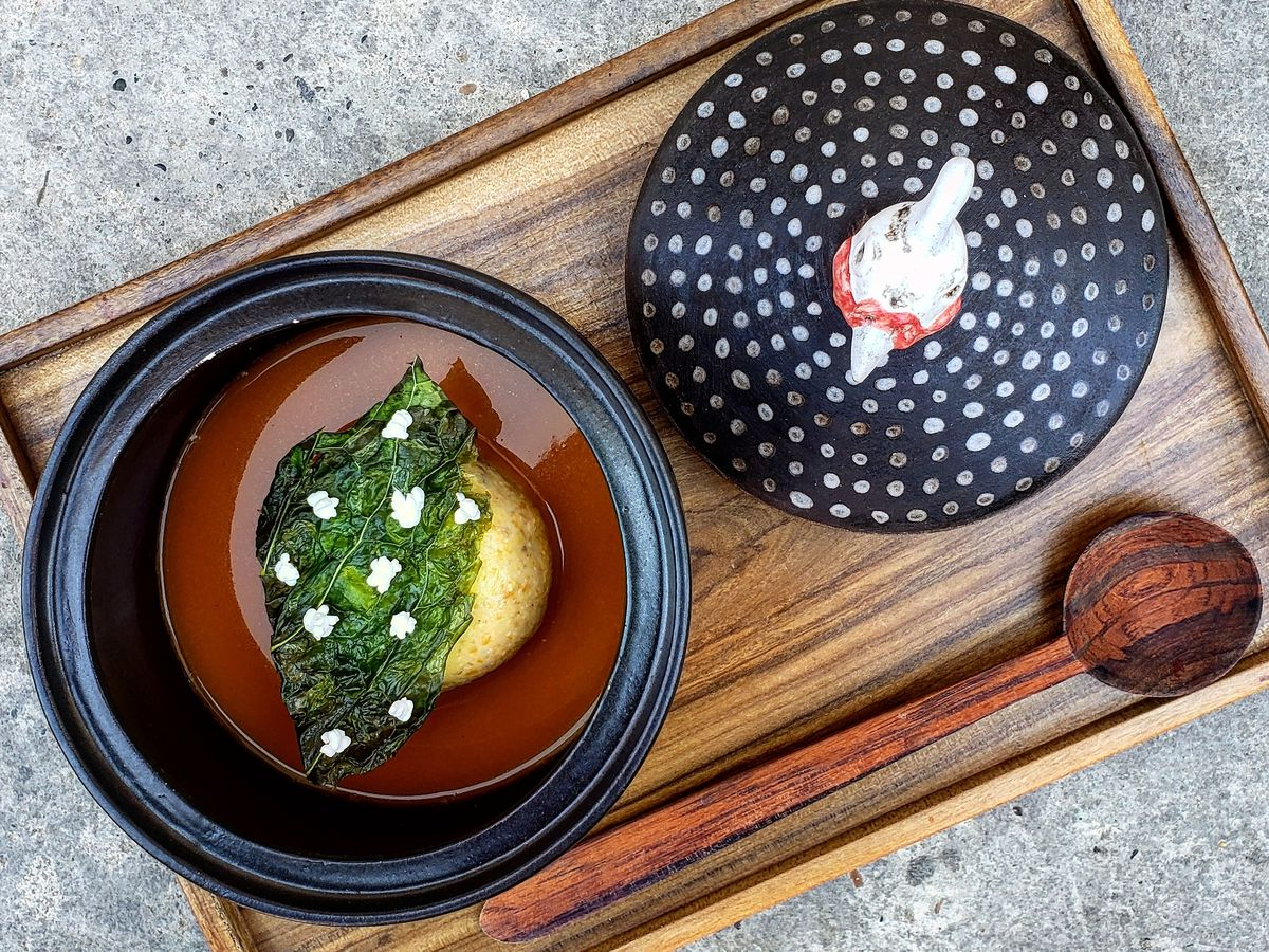 From above, two dishes sit on a wood tray with a long wooden spoon, one with a corn bun beneath shards of greens dotted with white flowers, the other a pipe-like object on a decorative plate