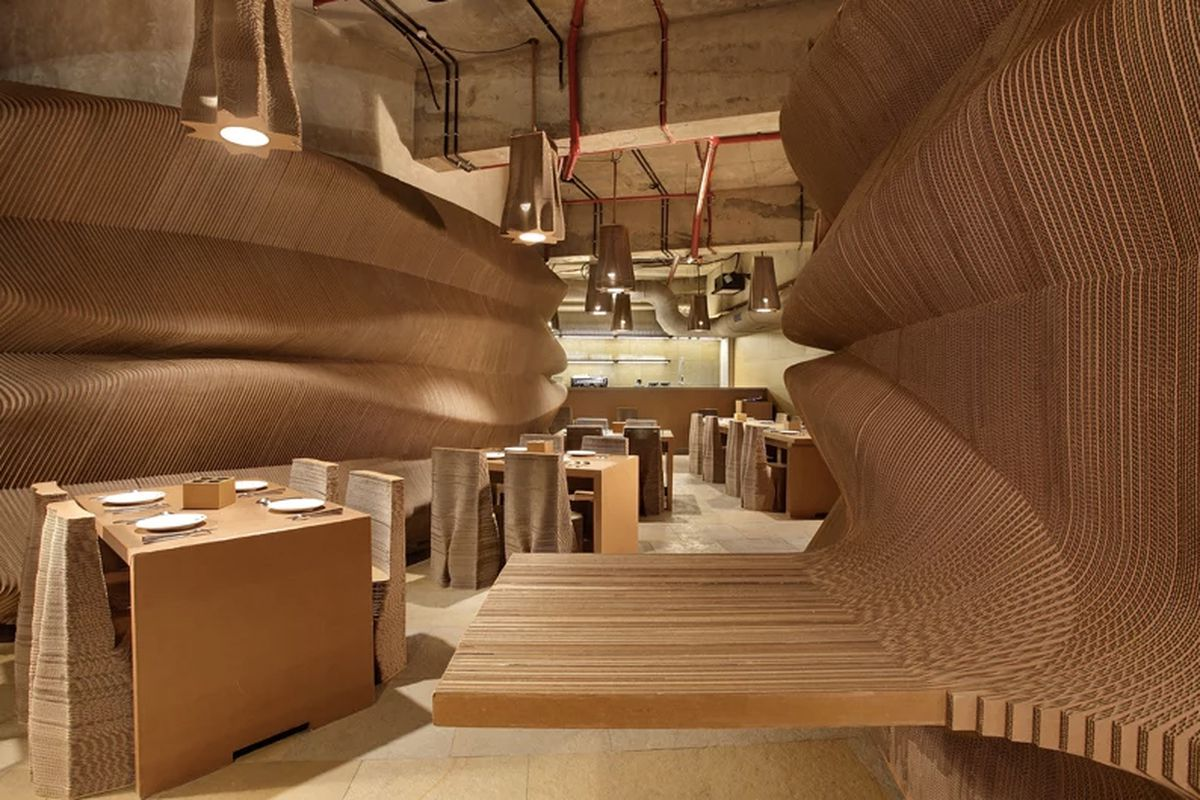 The interior of a cafe in India. The walls, chairs, counters, and light fixtures are made of cardboard.
