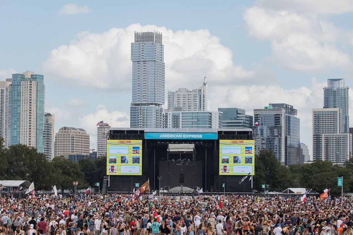 A large crowd gathered outside in front of a large stage. There is a row of tall buildings in the background. The sky is partly cloudy.