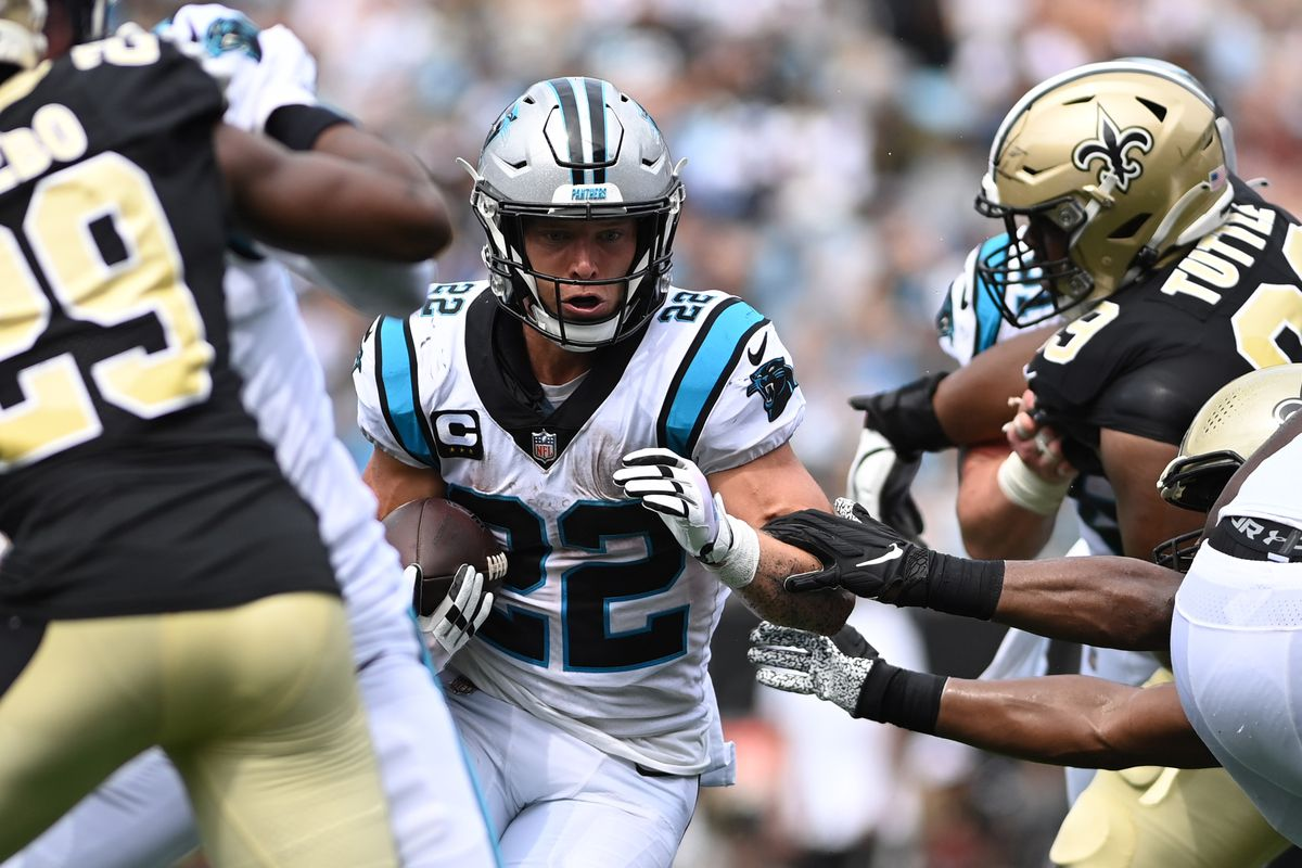Carolina Panthers running back Christian McCaffrey (22) runs as New Orleans Saints cornerback Paulson Adebo (29) and defensive tackle Shy Tuttle (99) defend in the second quarter at Bank of America Stadium.