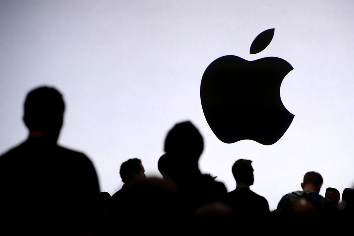 An Apple logo surrounded by silhouetted people