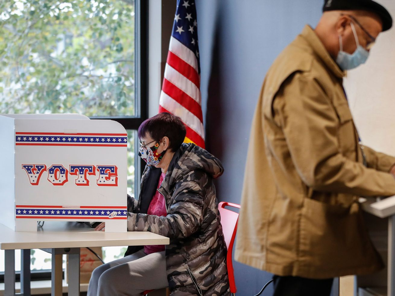 People voting at an indoor polling location.