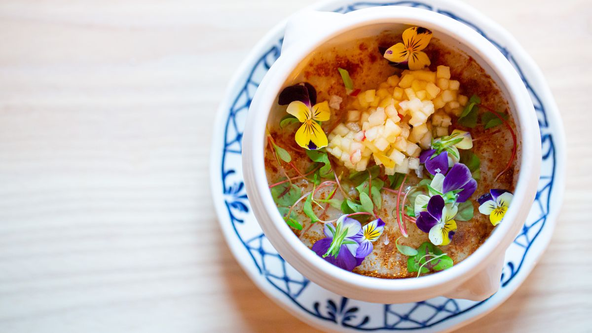 A ceramic blue and white bowl of gold rice pudding garnished with edible violets at Little Bear Atlanta