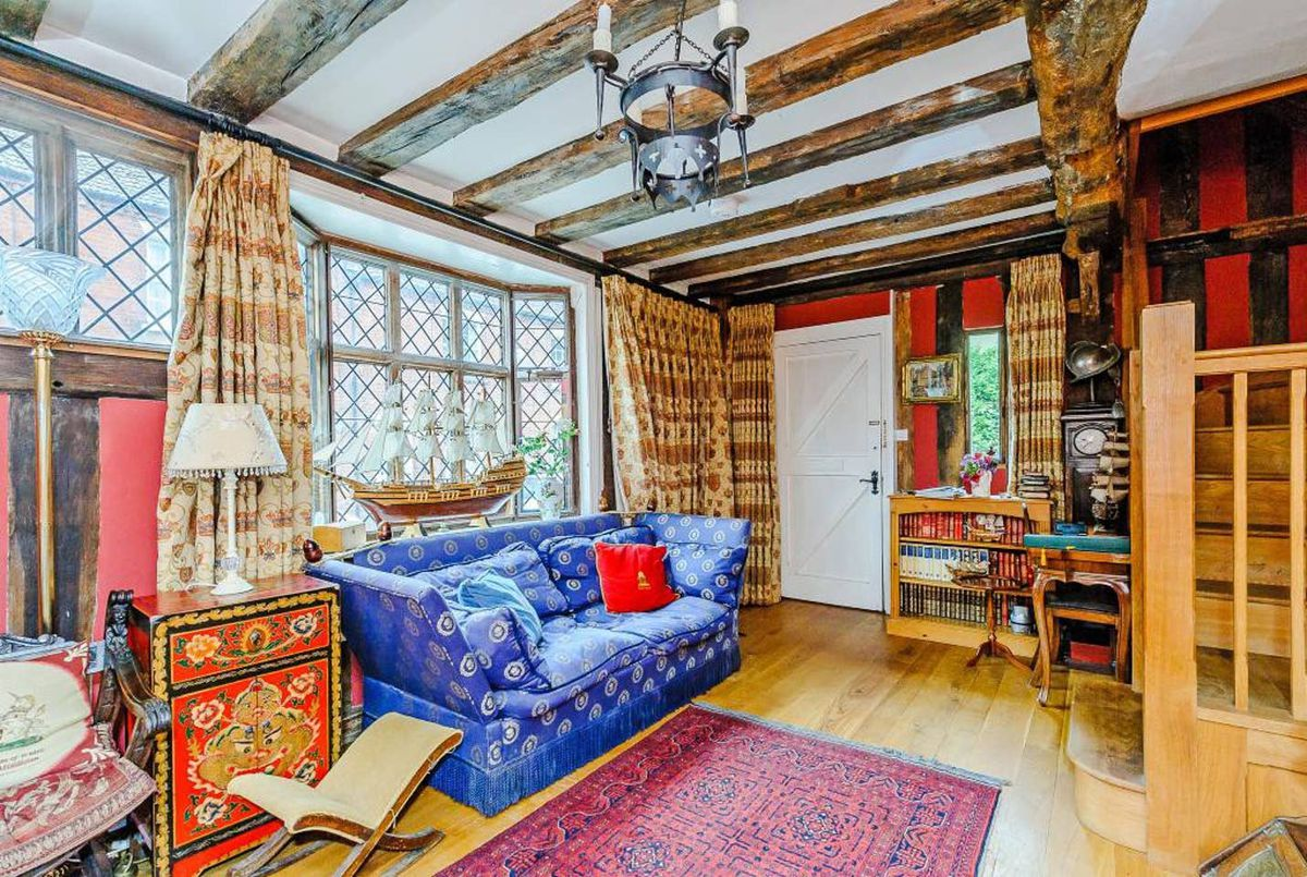Sitting room with timber beam ceiling and blue sofa.