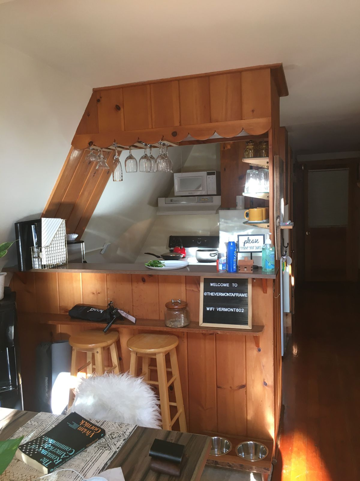 The cabin's kitchen, shown with a table and two stools in the foreground and small kitchen appliances in the background.