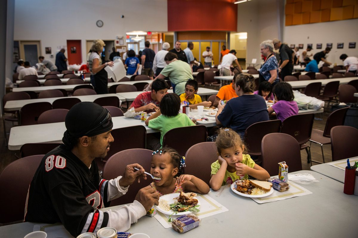 A man eats with two children at a soup kitchen