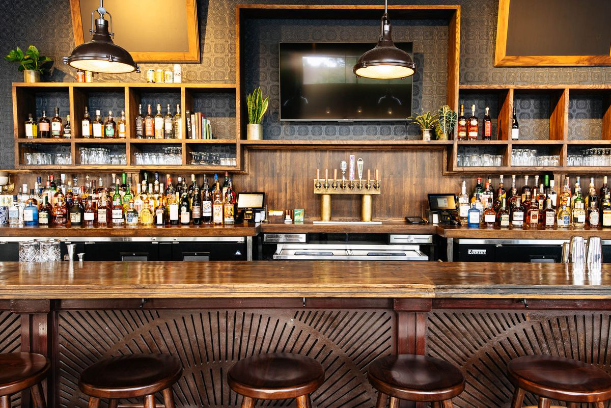 Hand-carved wooden bar lined with liquor bottles and plants