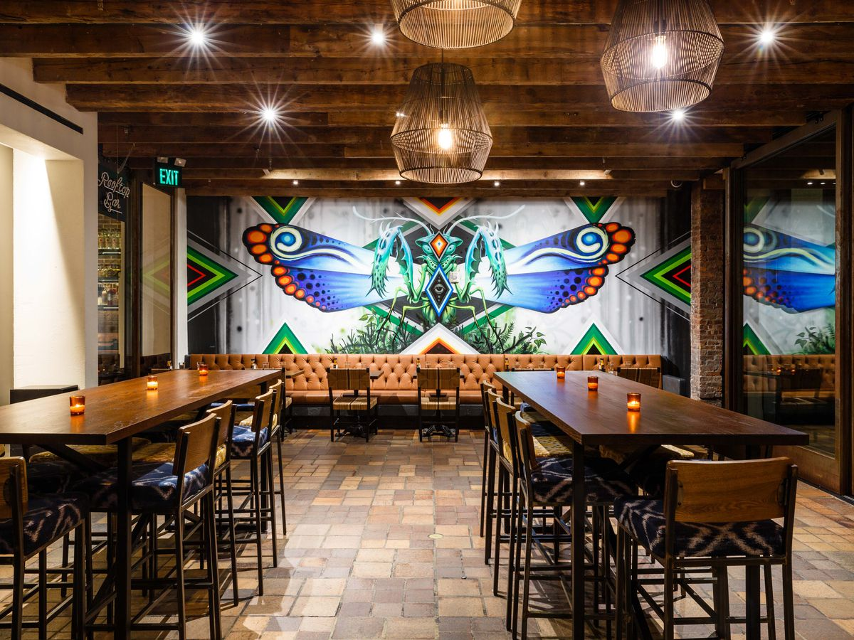 Empellon Al Pastor Midtown's dining room has two long communal tables and a mural on the back wall.