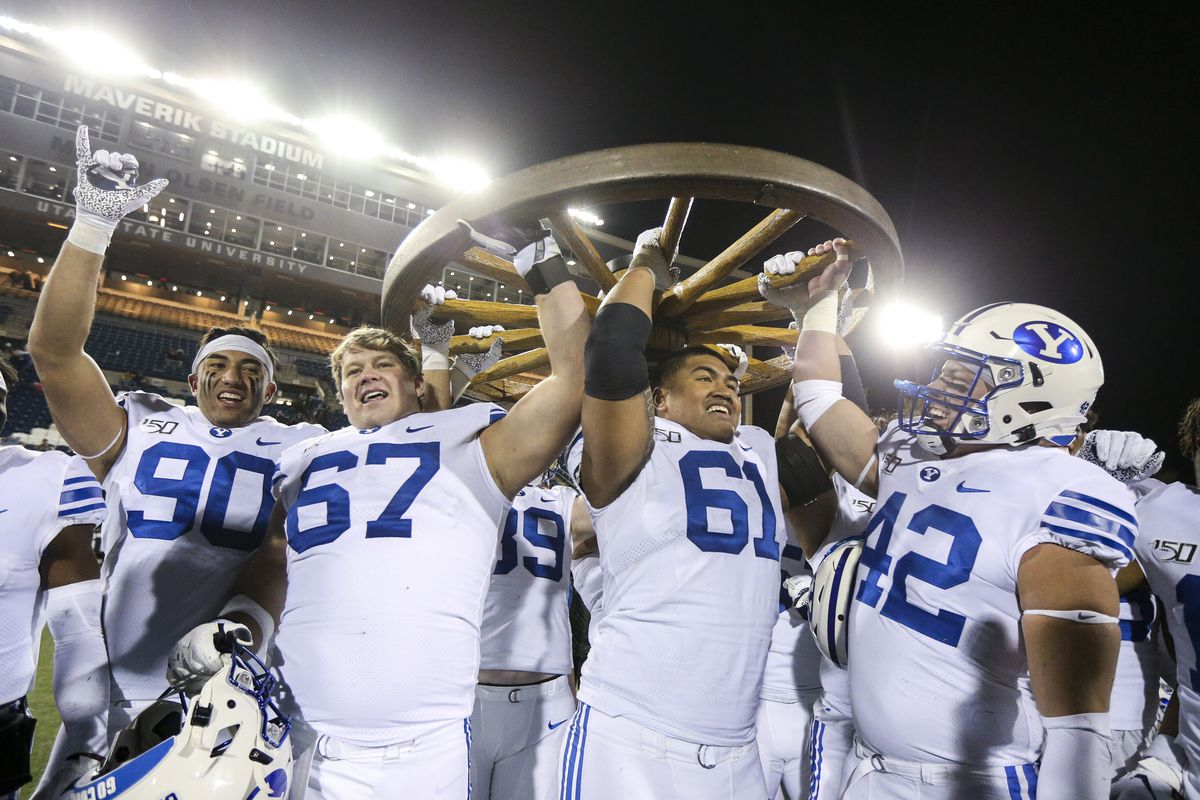 The Brigham Young Cougars lift the Old Wagon Wheel following their 42-14 win over the Utah State Aggies.