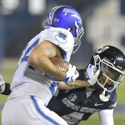 Air Force running back Kadin Remsberg (24) is tackled by Utah State safety Shaq Bond (4) during the first half of an NCAA college football game Thursday, Dec. 3, 2020, in Logan, Utah.