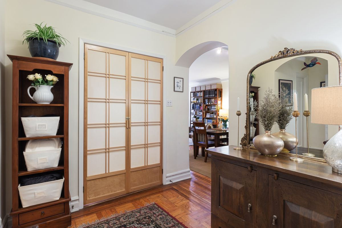 An arched entryway with beige walls, hardwood floors, and wooden furniture.