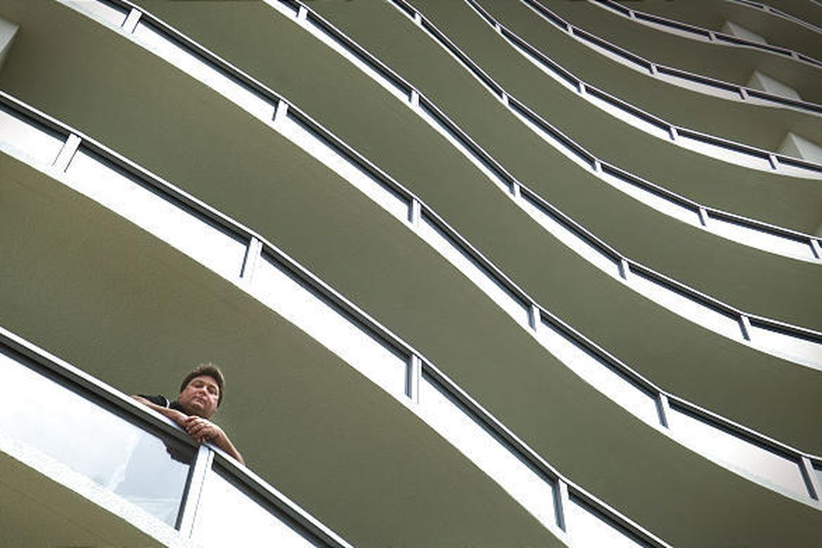Victor Vangelakos looks out from his seventh-floor condo balcony. The Vangelakoses are the building's only tenants.