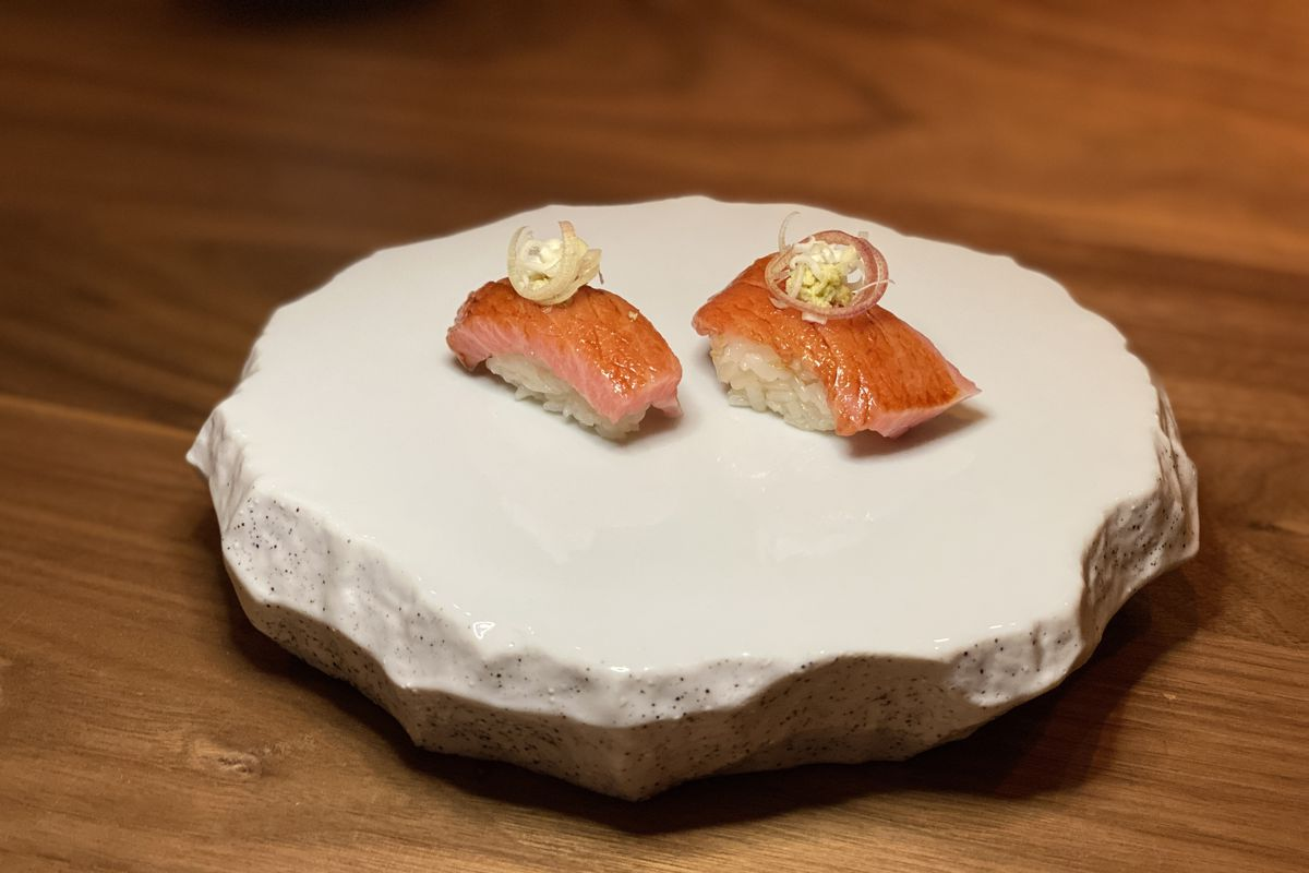 Salmon nigiri served on a circular white stone platter