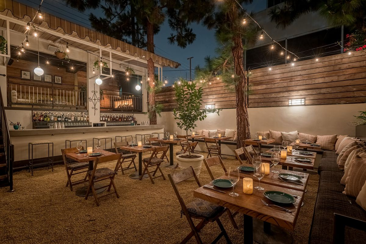 An outdoor bar with wooden table seating at night.
