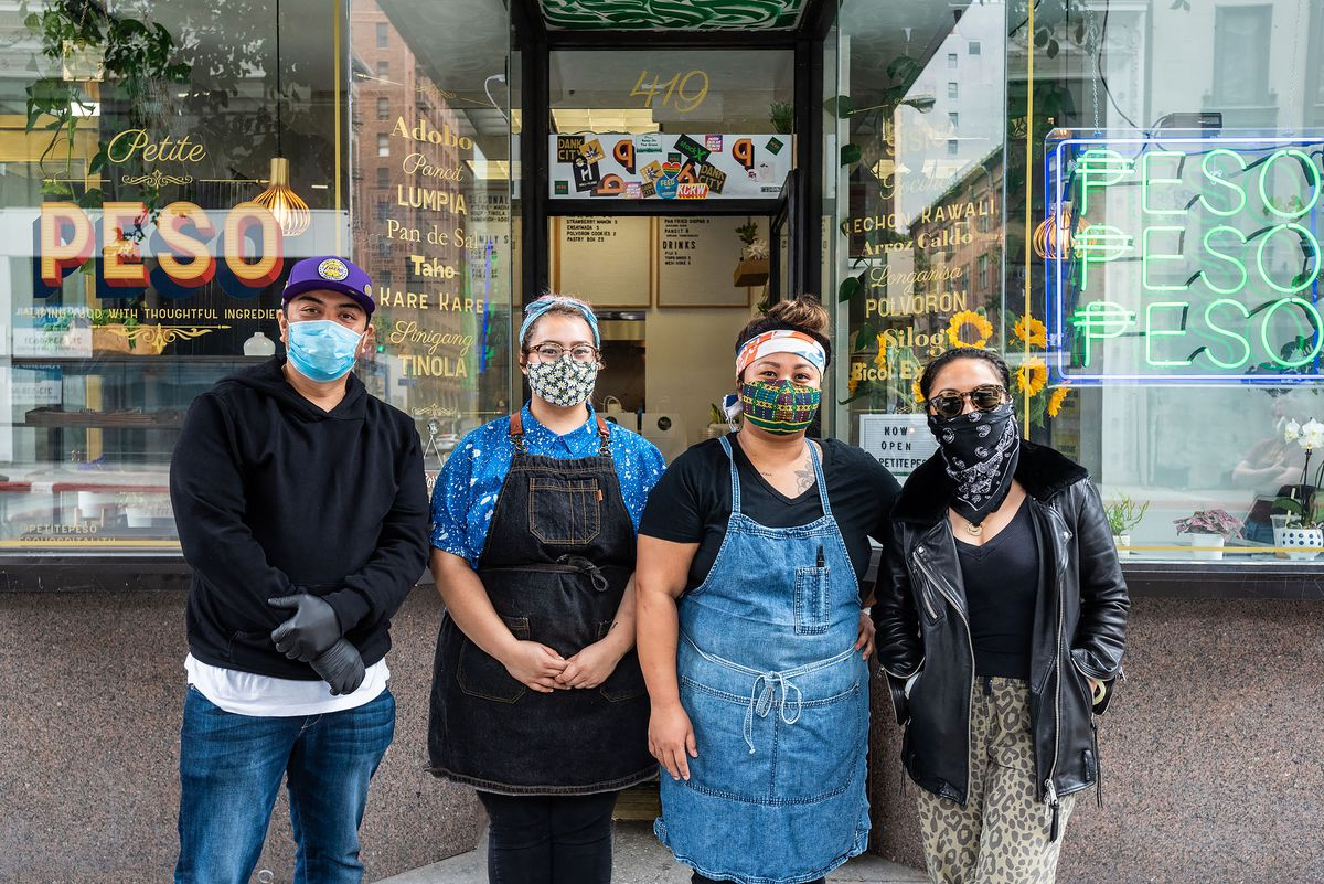 A team of restaurant workers stands, wearing masks, in front of their restaurant.