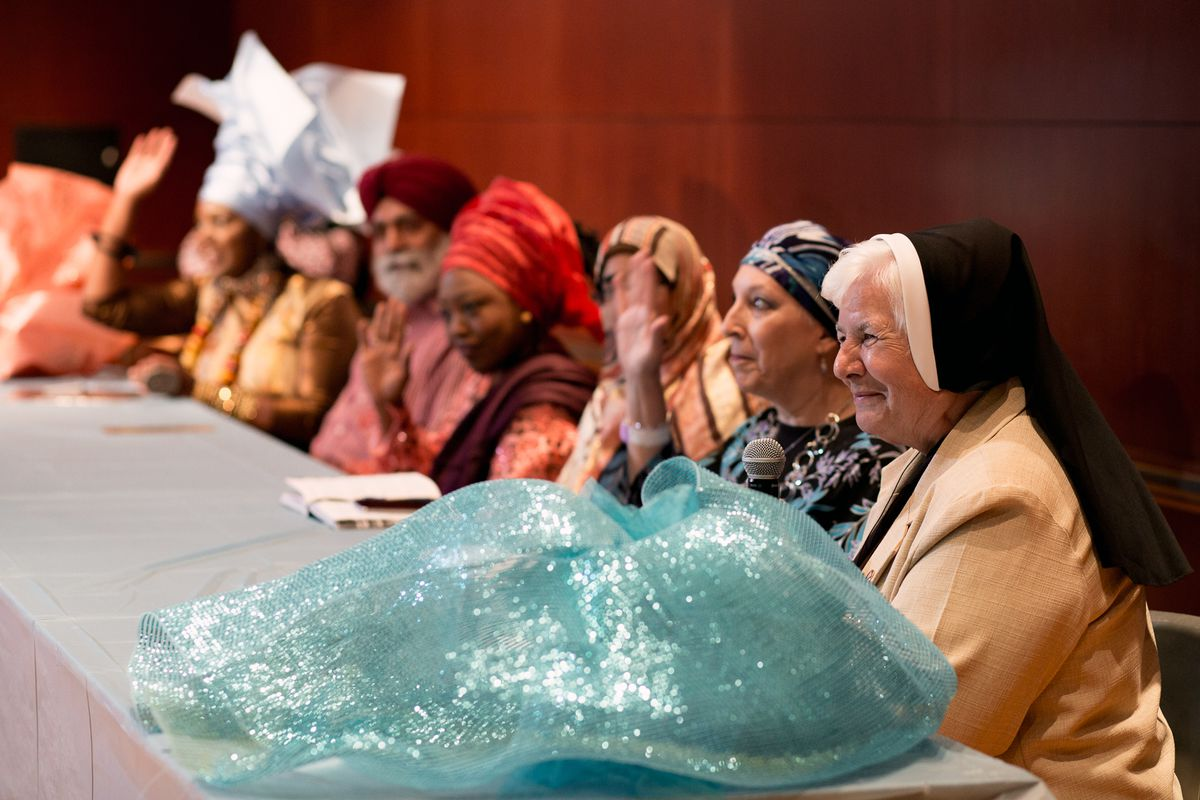People in different head coverings sit at a table during an interfaith panel at the expo.