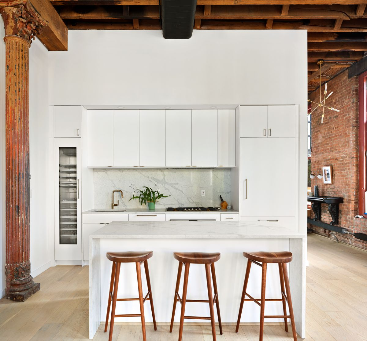 A kitchen with white cabinetry and a wine fridge.