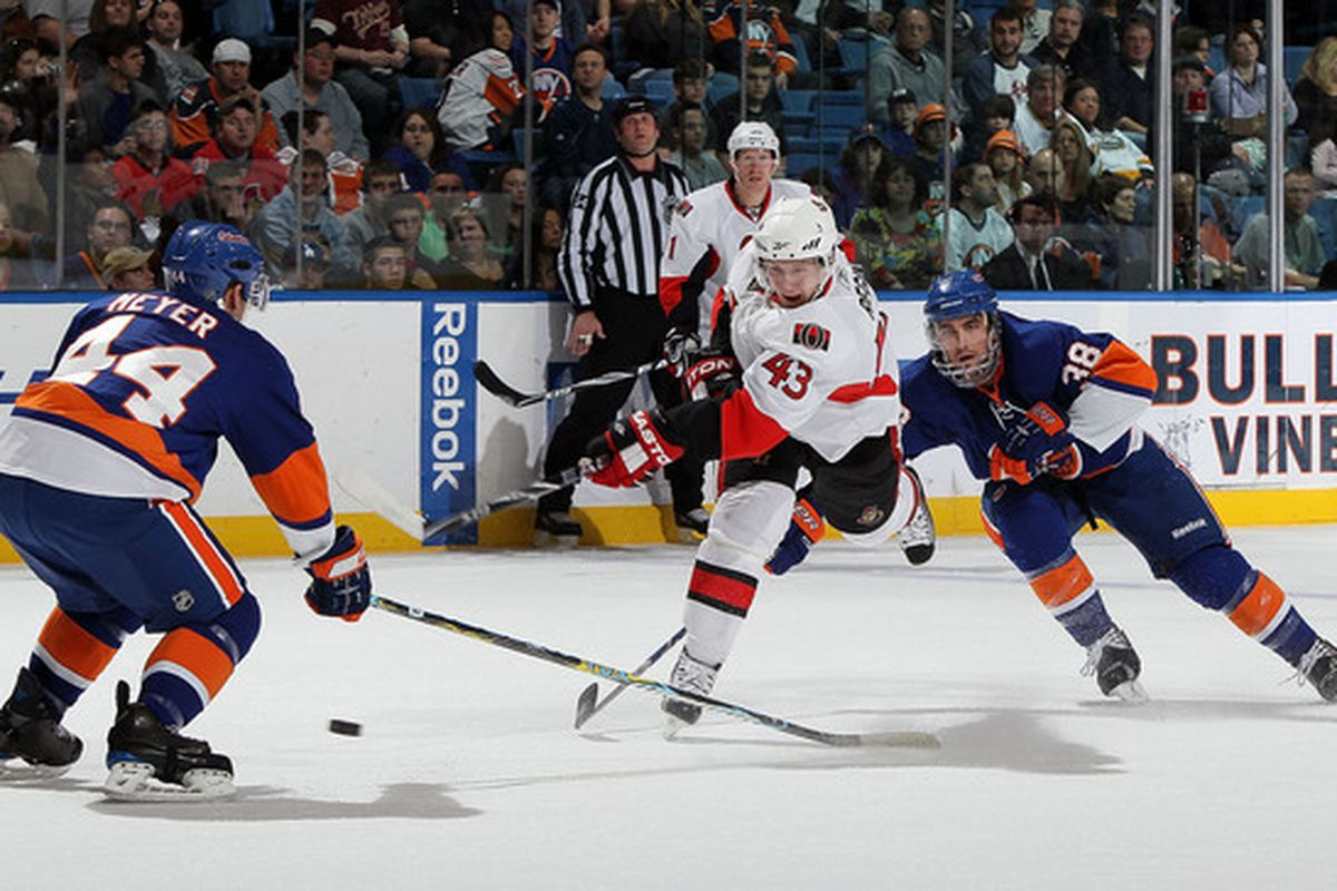 UNIONDALE, NY - APRIL 03:  Peter Regin #43 of the Ottawa Senators fires the puck against Freddy Meyer #44 and Jack Hillen #38 on April 3, 2010 at Nassau Coliseum in Uniondale, New York.  (Photo by Jim McIsaac/Getty Images)